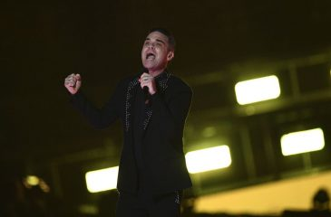 Robbie Williams apareció con estrafalario look en desfile de Armani