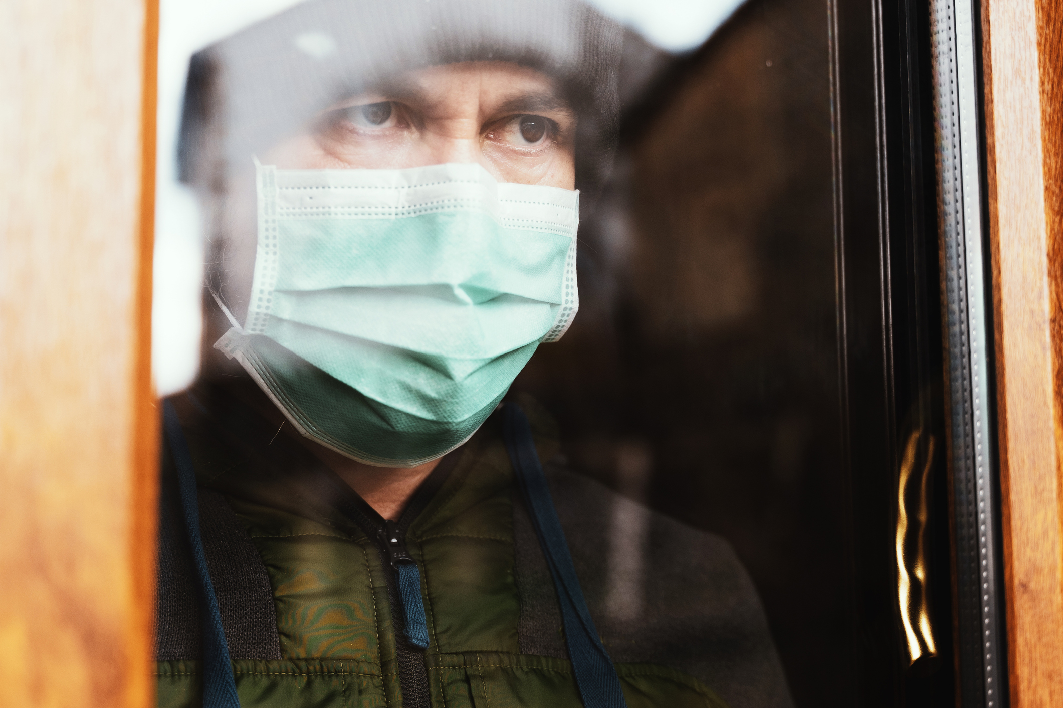An Infected Man On Quarantine At Home Wearing A Face Mask At Home And Looking Through The Window